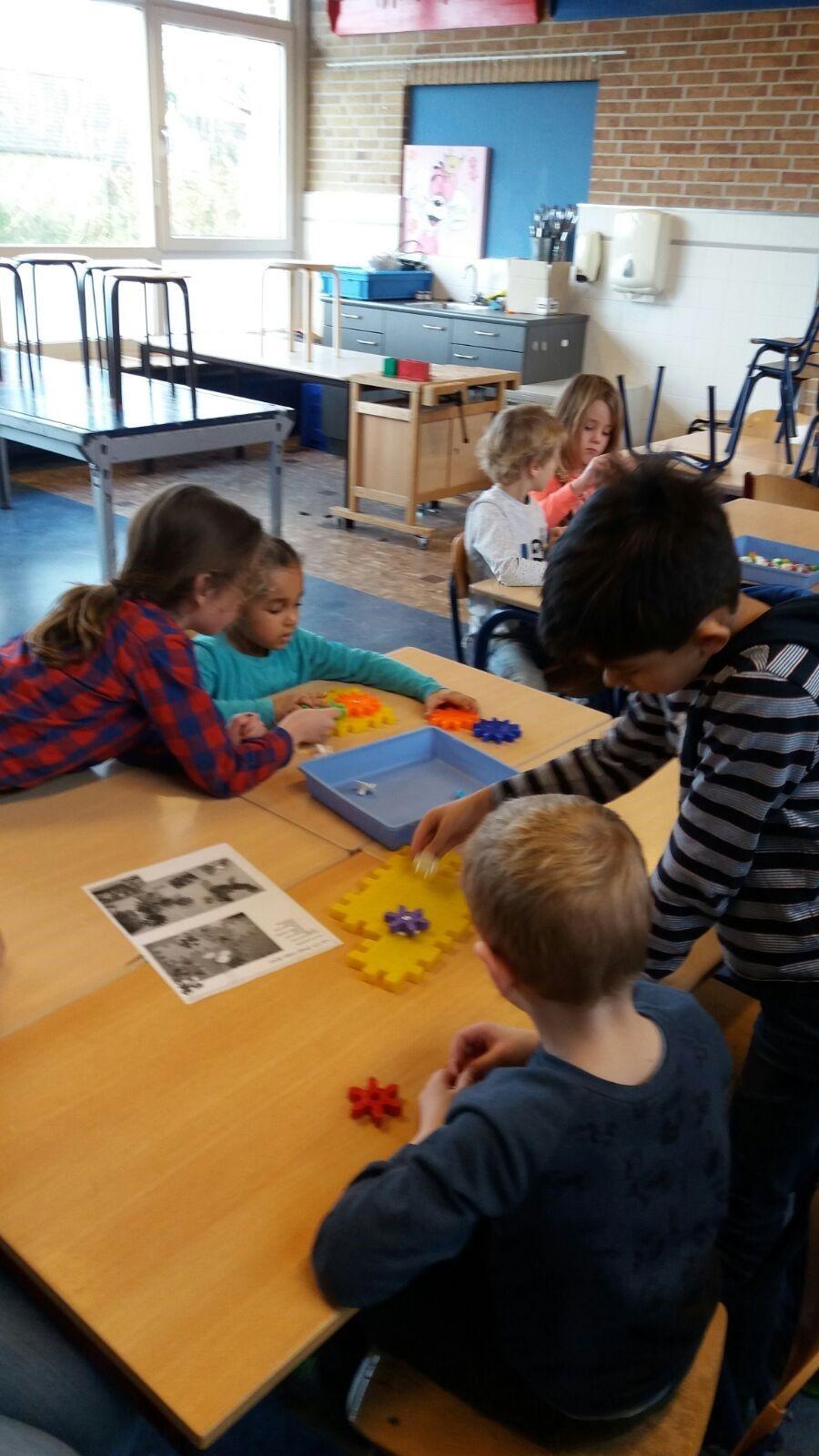 """Hier nog wat foto's van groep 5 met onze maatjesklas. Juf Carla en juf Marja helpen ons elke woensdag met een circuit (spelletjes, bouwen, techniek etc.). Op foto 1 zie je Marlow hij helpt zijn maatje: """"Ik ben bezig met tandwielen want als je aan 1 ding gaat draaien, gaat alles draaien"""". Op foto 2 is Femke aan het helpen:""""We zijn met tandwielen bezig, we klikken ze aan elkaar en dan gaat alles rond."""" Op foto 3 zie je Rive: """" We proberen de tandwielen in elkaar te zetten en dan gaan ze bewegen, soms lukt het niet, dan halen we ze eruit en proberen we op een andere plek te zetten zodat het wel gaat bewegen"""". Op foto 5 is Faith aan het helpen: """" Als je tandwielen niet zo dicht op elkaar zet, kunnen ze beter draaien. En als je ze dichter op elkaar zet dan draaien ze niet""""."""